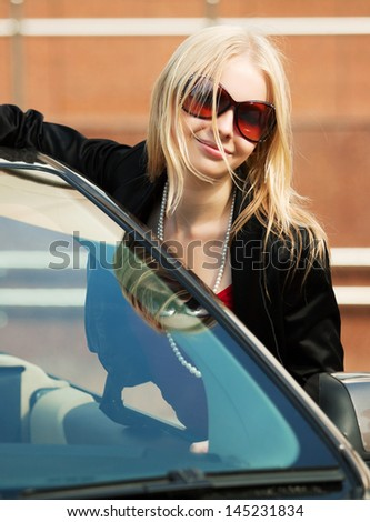 Happy young blond woman with at the car