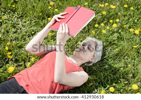 happy young blond woman with book on flower meadow - stock photo