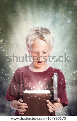 Happy Young Blonde Boy Opening a Gift Box - stock photo