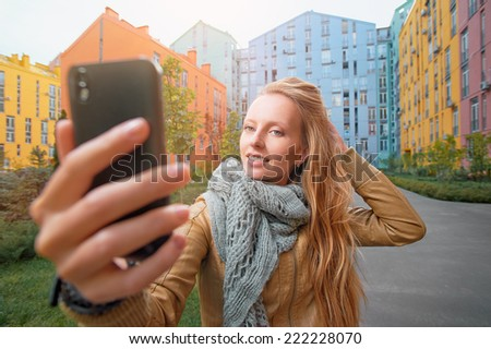 Happy young blonde caucasian woman taking a selfie portrait with mobile phone at the colored buildings background - stock photo