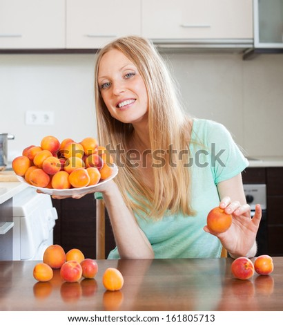 Happy young blonde housewife with heap of apricots t domestic kitchen