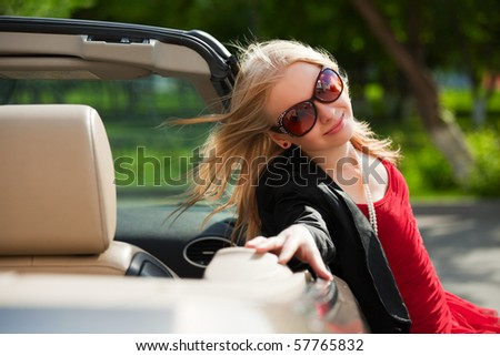 Happy young blonde with a convertible. - stock photo