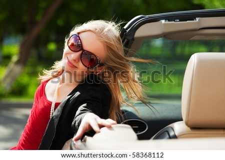 Happy young blonde with a convertible.