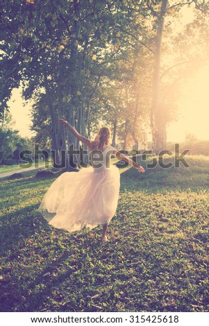 happy young blonde woman in white t-shirt and long pink tulle skirt dance in park, full body shot, retro colors - stock photo