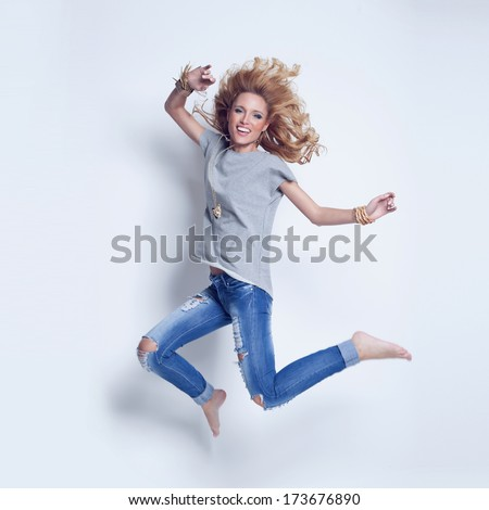 Happy young blonde woman jumping. Fashionable attractive girl in funny pose. - stock photo