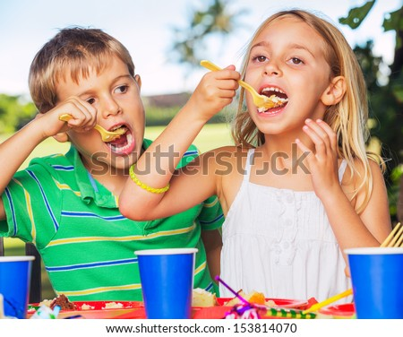 Happy Young Boy and Girl Eating Cake at Birthday Party - stock photo