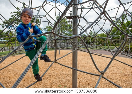 Happy young boy climbing to the top at outdoor playground