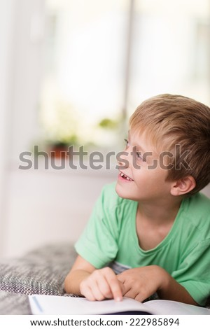 Happy young boy doing his homework looking off to the left of the frame with a cheeky smile as he sits reading his classwork - stock photo