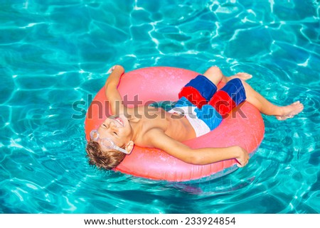 Happy Young Boy Floating in Swimming Pool on Raft - stock photo