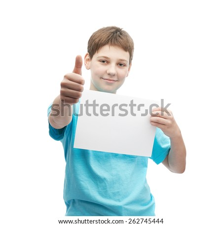 Happy young boy in a cyan t-shirt with a empty copyspace A4 sheet of paper in front of him while showing thumbs up sign, composition isolated over the white background - stock photo