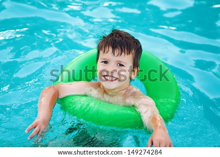 Happy young boy in pool with saver learning swim, childhood