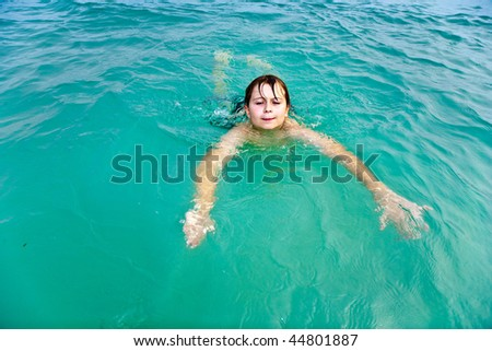 happy young boy is swimming in the warm clear sea and enjoying the vacation