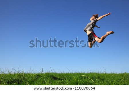 Happy young boy jumping in the meadow - stock photo