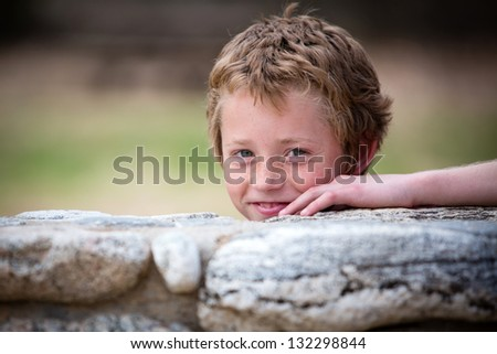 Happy young boy leaning against some rocks smiling - stock photo