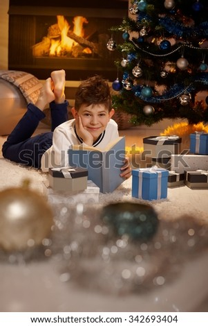 Happy young boy lying by christmas tree, reading book, smiling, looking at camera. - stock photo
