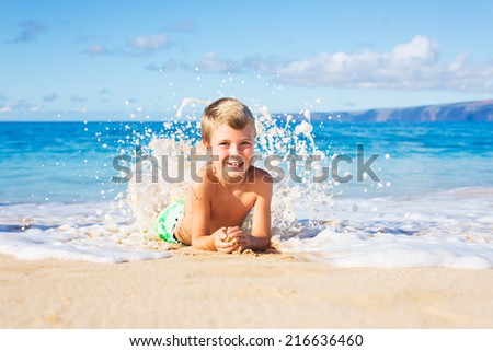 Happy Young Boy on the Beach Lying in the Sand Playing in the Waves - stock photo