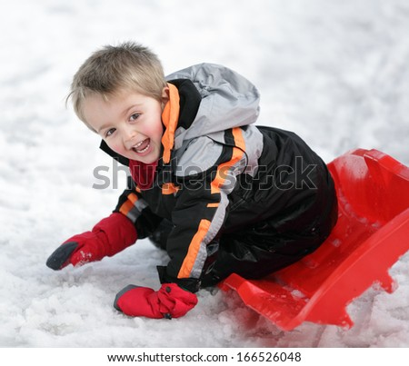 Happy young boy out playing in the snow on his sledge - stock photo