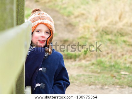 happy young boy playing at the park on a cold day