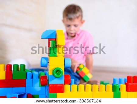 Happy young boy playing with his building blocks holding a finished creation in his hands as he grins cheekily at the camera