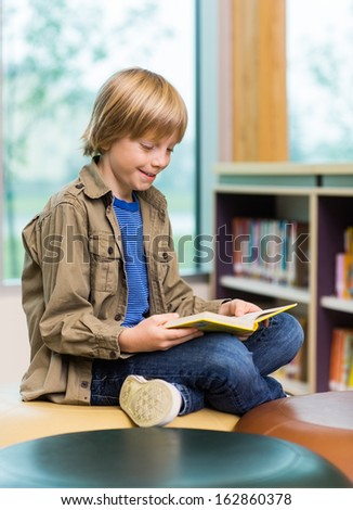 Happy young boy reading book in school library