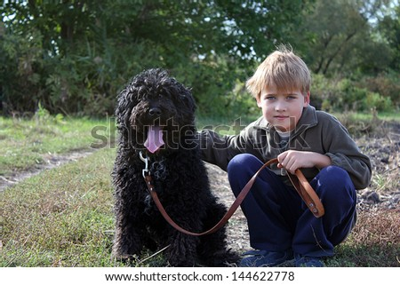 Happy young boy resting with his dog in the field - stock photo