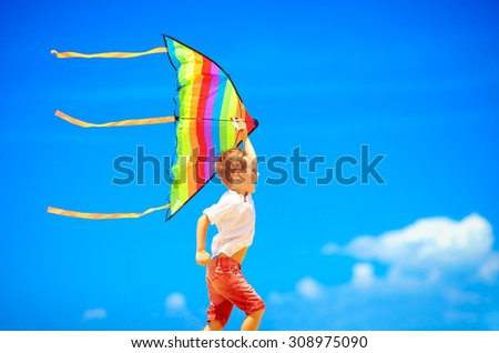 happy young boy running with kite on sky background - stock photo