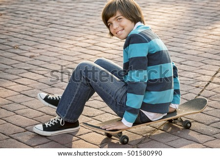 Happy young boy sitting on his skateboard, cobblestone pavement
