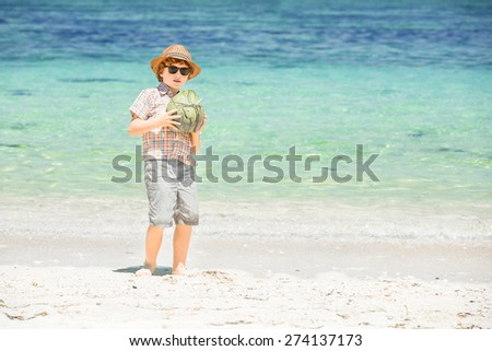 Happy young boy staying on beautiful ocean beach wearing hat and sunglasses holding green coconut in his heands and enjoing summer time