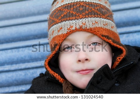 happy young boy with blue eyes wearing a hat smiling - stock photo