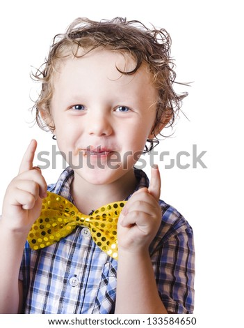 Happy young boy with bow tie pointing upwards, white background