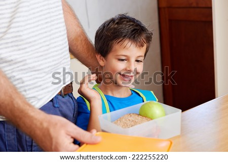 happy young boy with dad and healthy food apple in lunch box for school - stock photo