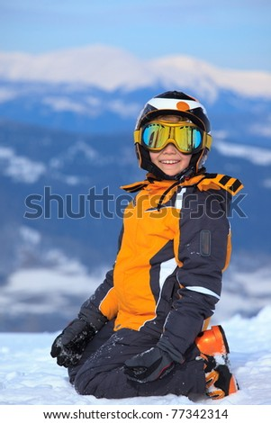 Happy young boy with ski helmet and goggles or mask on snow Alpine mountain peak. - stock photo