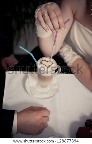 Happy young bride and groom drink a cup of Coffee latte with heart design on their wedding day. Wedding couple - new family! wedding dress. Bridal wedding bouquet of flowers - stock photo