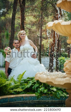 Happy young bride and groom outdoors in the park on their wedding day. Wedding couple - new family! wedding dress. Bridal wedding bouquet of flowers