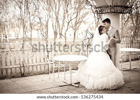 Happy young bride and groom outside on their wedding day. Wedding couple - new family! wedding dress. Bridal wedding bouquet of flowers - stock photo