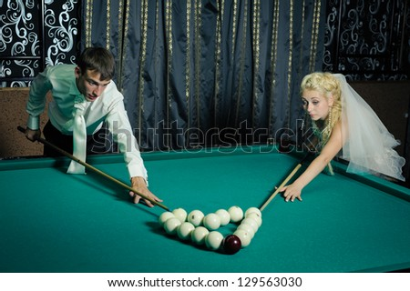 Happy young bride and groom playing billiard at night on their wedding day. Young newlyweds playing billiards at their mansion. Wedding couple. wedding dress. Bridal wedding bouquet of flowers - stock photo