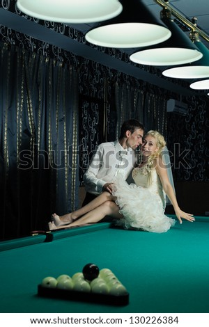 Happy young bride and groom playing billiard at night on their wedding day. Young newlyweds playing billiards at their mansion. Wedding couple. wedding dress. Bridal wedding bouquet of flowers
