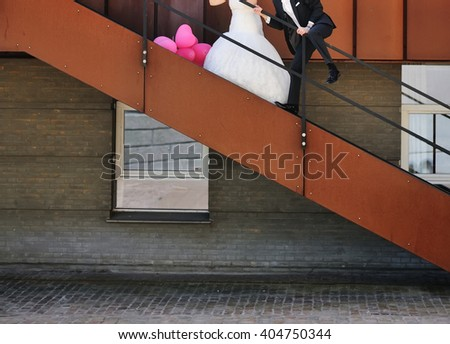 Happy young bride and groom together, wedding couple with pink ballons walking in Copenhagen  - stock photo