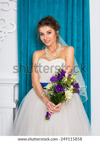 Happy young bride in white studio