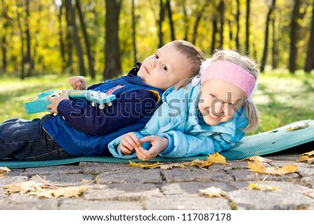 Happy young brother and sister playing together on a mat outdoors in a park