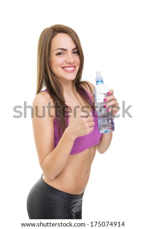 Happy young brunette Caucasian fitness woman drinking water gesturing thumbs up isolated on white background. Fitness, diet and healthy lifestyle concepts. - stock photo