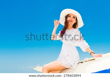 Happy young brunette in a white straw hat and white dress sitting on an old fishing boat on a tropical beach. Summer vacation concept. - stock photo