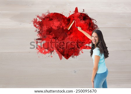 Happy young brunette painting with roller against bleached wooden planks background - stock photo