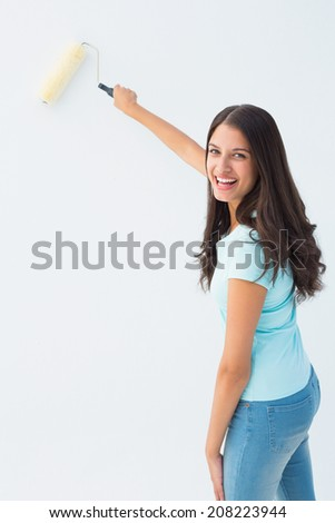 Happy young brunette painting with roller on white background - stock photo