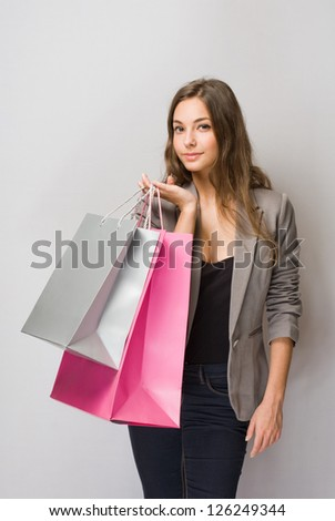 Happy young brunette shopper with colorful shopping bags. - stock photo