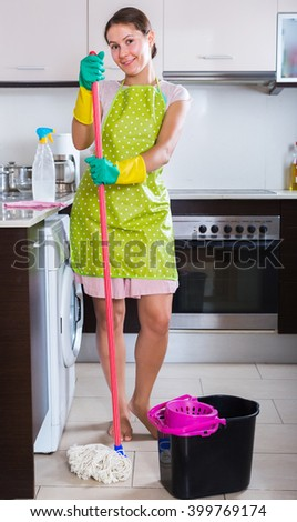 Happy young brunette with mop and bucket in domestic interior