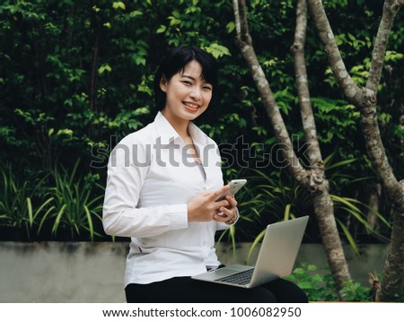Happy young business Asian woman using laptop in coffee shop.