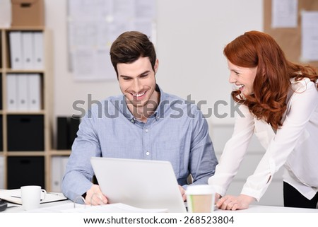 Happy Young Business Couple Watching Something at Laptop Computer on Top of the Office Table. - stock photo