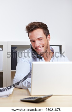 Happy young business in office making a phone call - stock photo