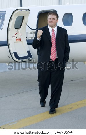 Happy young business man celebrating in front of corporate jet. - stock photo